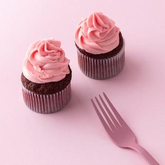 High angle cupcakes mit rosa zuckerguss und gabel