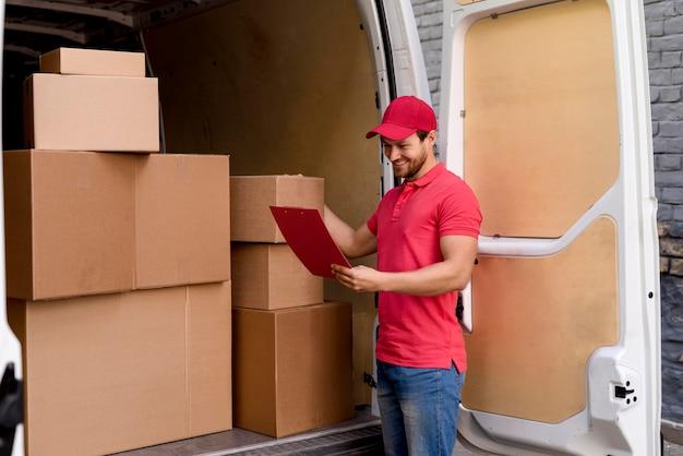 High angle delivery man prüft paketliste