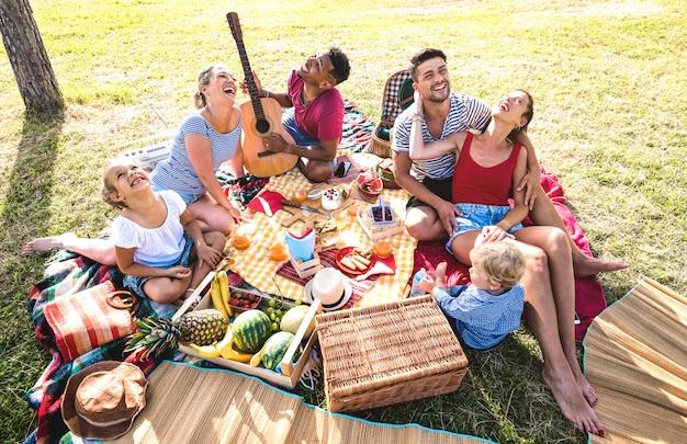 High angle draufsicht auf glückliche familien, die spaß mit kindern bei pic nic grillparty haben
