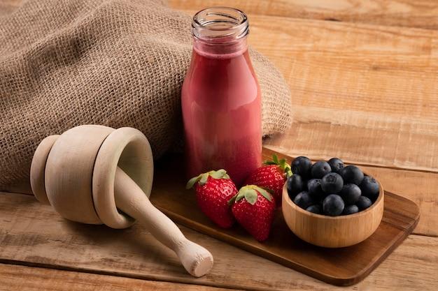 High angle erdbeeren und blaubeeren mit smoothie