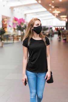 High angle frau im einkaufszentrum trägt maske