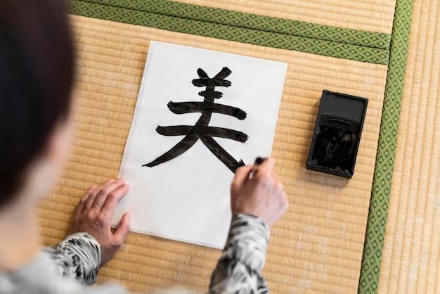 High angle frau malt japanisches symbol
