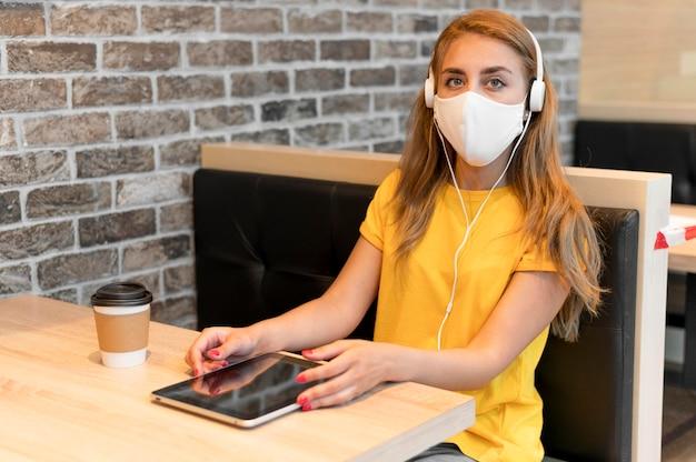 High angle frau mit tablette tragende maske