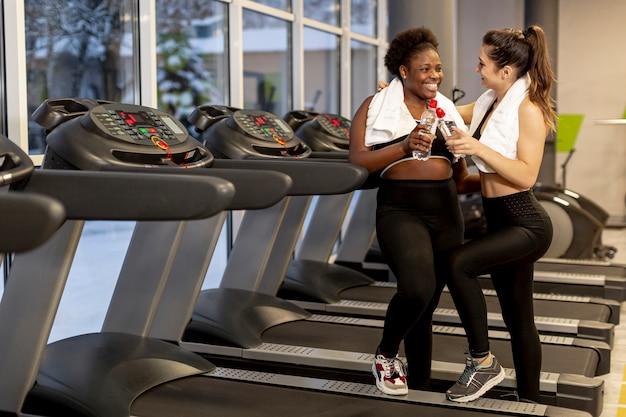High angle frauen im fitnessstudio sprechen