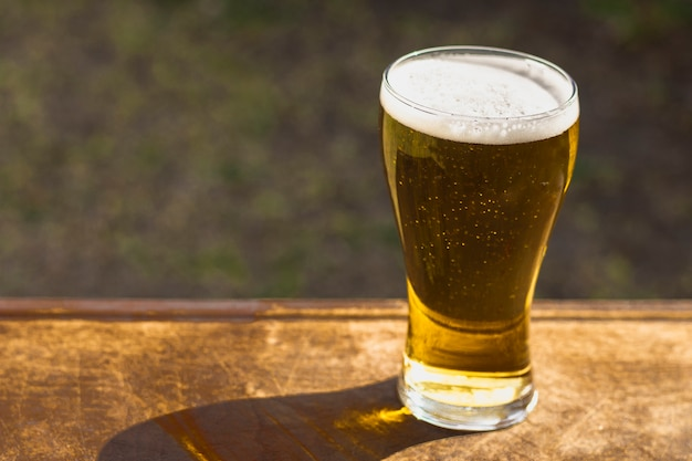 High angle glass mit schäumendem bier auf dem tisch