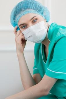 High angle krankenschwester trägt maske