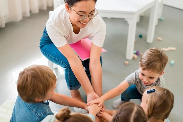High angle lehrerin spielt mit ihren schülern im kindergarten