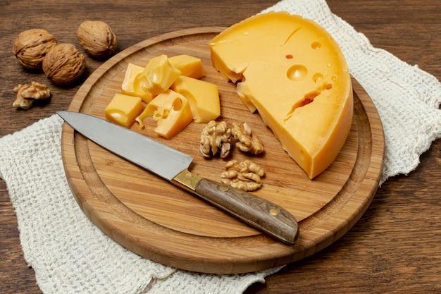 High angle messer und käse auf einem brett