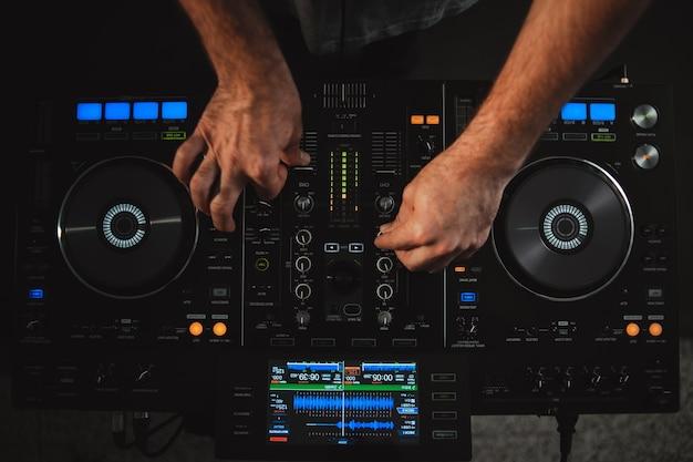 High angle nahaufnahme eines dj, der unter den lichtern in einem studio arbeitet