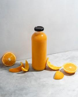 High angle orangen und saftflasche