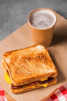 High angle sandwich mit speck und käse mit kaffee