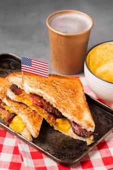 High angle sandwich mit speck und käse mit pommes