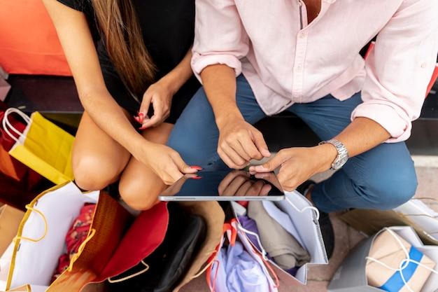High angle shopping paar tablet halten