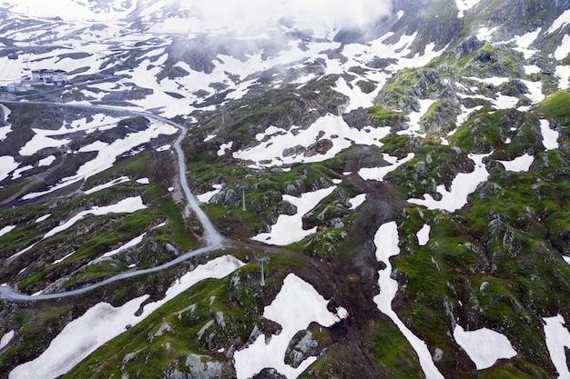 High angle shot des schneebedeckten feldes an einem nebligen tag eingefangen