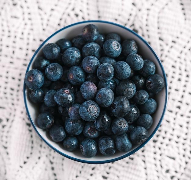 High angle shot einer mit blaubeeren gefüllten schüssel auf einer schönen weißen tischdecke auf einem tisch