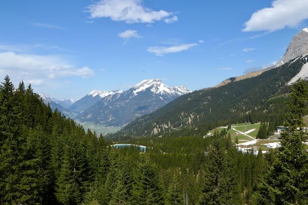 High angle shot einer schönen bergkette mit grünen tannen und schnee unter bewölktem himmel bedeckt
