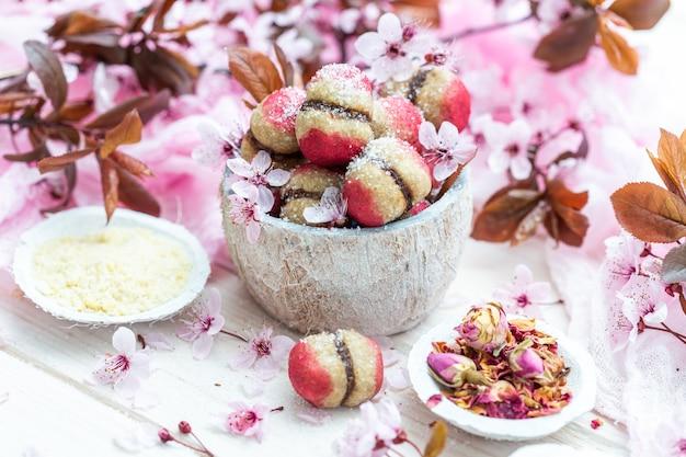 High angle shot einer schüssel mit köstlichen veganen pfirsichkeksen, umgeben von kleinen blumen
