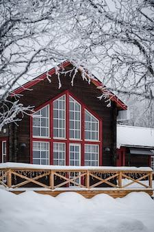 High angle shot einer straße in einem wald mit einer person, die darauf steht, bedeckt im schnee