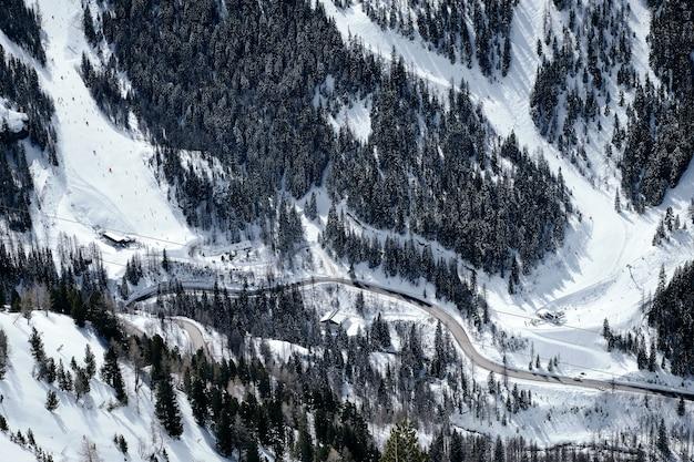 High angle shot eines bewaldeten, schneebedeckten berges in col de la lombarde