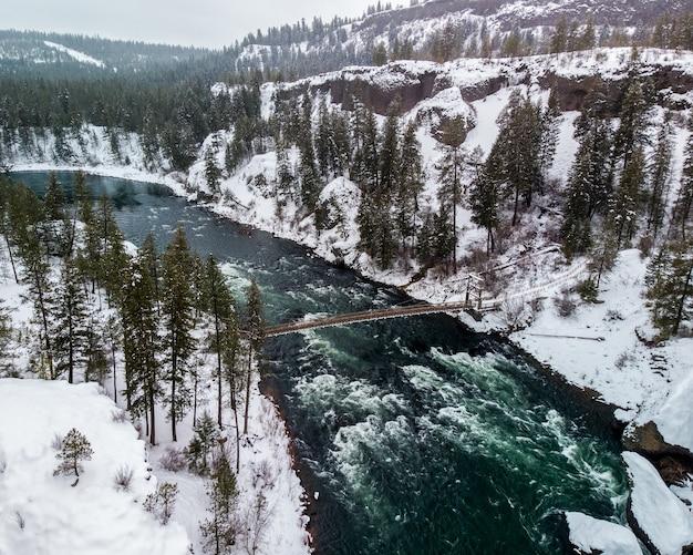 High angle shot eines flusses mitten in schneebedeckten bergen, die mit bäumen bedeckt sind