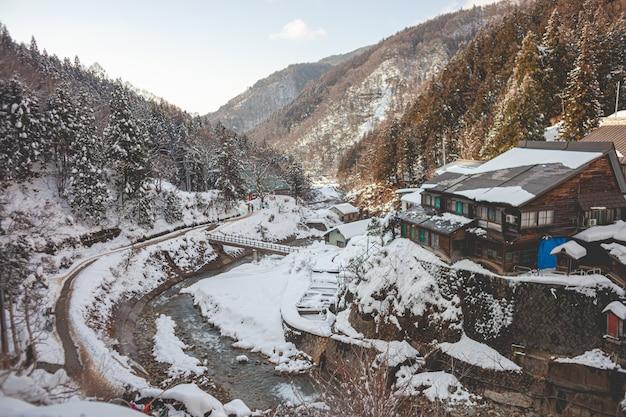 High angle shot eines holzhauses, umgeben von bewaldeten bergen, die im winter mit schnee bedeckt sind