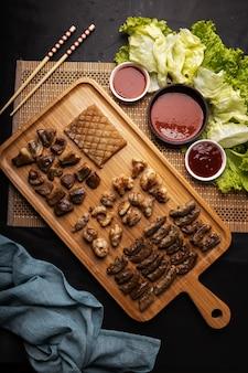 High angle shot eines holztabletts mit gebratenem fleisch, kartoffeln, gemüse und sauce auf einem schwarzen tisch