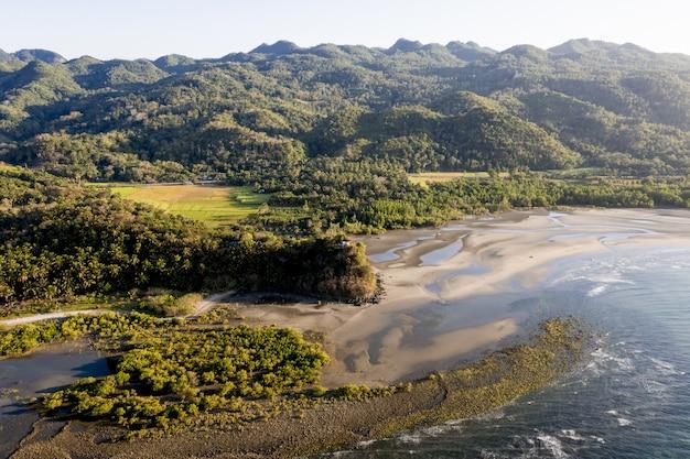 High angle shot eines meeres in der nähe eines ufers und berge, die tagsüber mit bäumen bedeckt sind