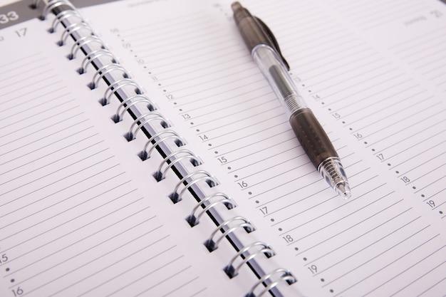 High angle shot eines stiftes auf einem offenen notizbuch
