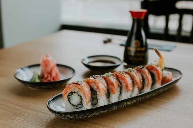 High angle shot eines tellers mit sushi und seinen zutaten auf einem tisch
