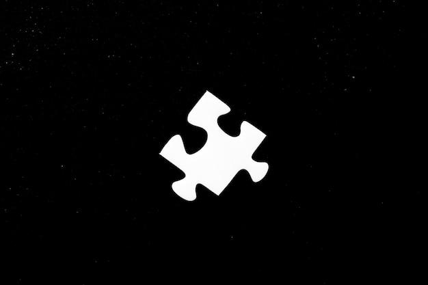 High angle shot eines weißen puzzleteils auf schwarzem hintergrund