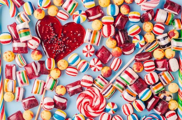 High angle shot von bunten bonbons und einem herzförmigen lutscher - perfekt für eine coole tapete