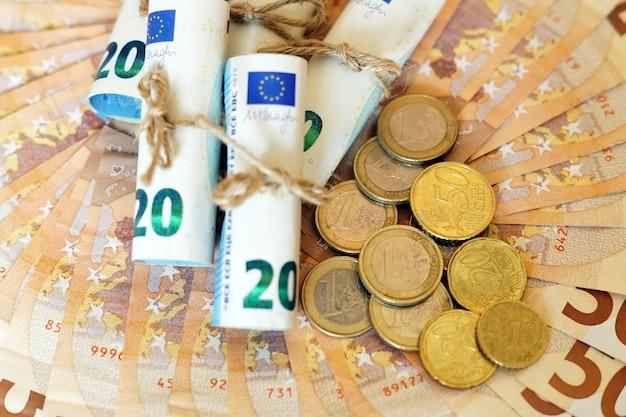High angle shot von einigen gerollten banknoten und münzen auf mehr banknoten