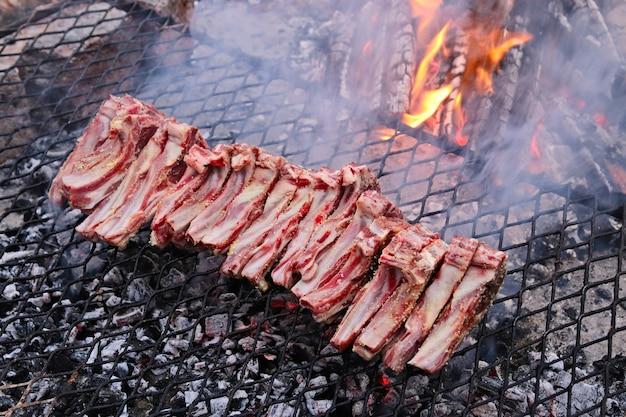 High angle shot von köstlichem fleisch, das auf dem feuer auf einem grill gekocht wird