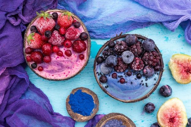High angle shot von köstlichen fruchtshakes mit gefrorenen früchten in kokosnussschalen
