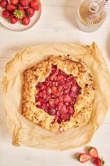 High angle shot von köstlichen rhabarber-erdbeer-gallate-kuchen mit zutaten auf einem weißen tisch