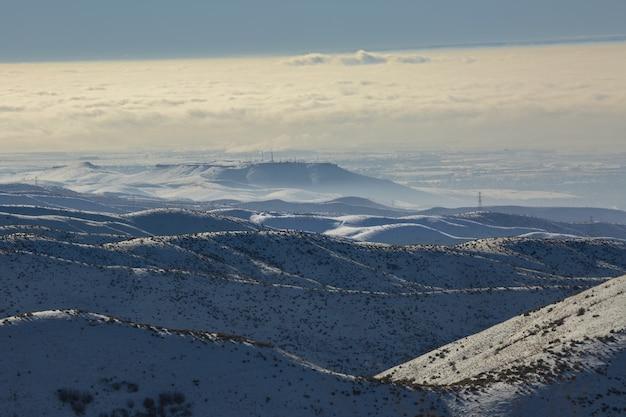 High angle shot von schneebedeckten bergen mit einem blauen bewölkten himmel am tag