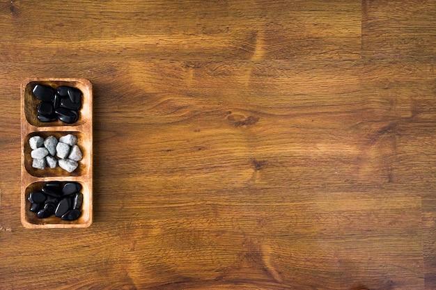 High angle shot von weißen und schwarzen steinen in einer holzplatte auf einer holzoberfläche