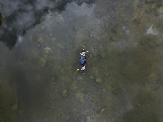 High angle shot von zwei personen auf einem ruderboot auf einem see