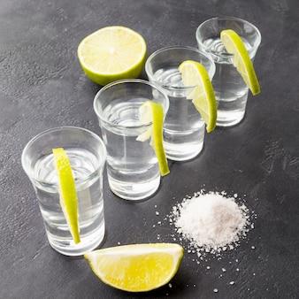 High angle silver tequila shots mit limettenscheiben und salz