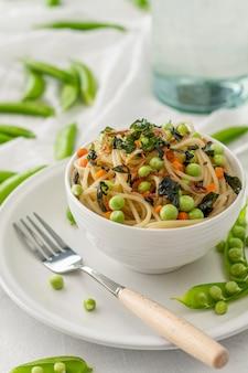 High angle spaghetti mit erbsen und gemüse