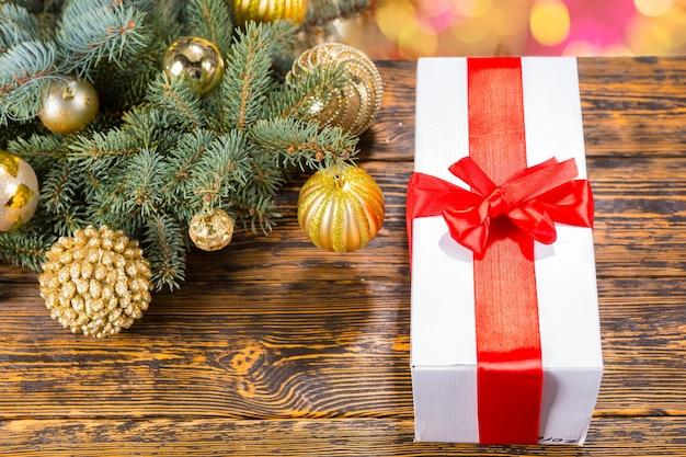 High angle still life of white box geschenk verpackt in roter schleife und auf dem tisch mit holzmaserung und textfreiraum neben festlichem weihnachtskiefernzweig, verziert mit goldenen kugeln