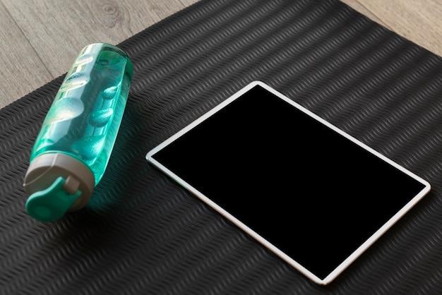 High angle tablet und wasserflasche