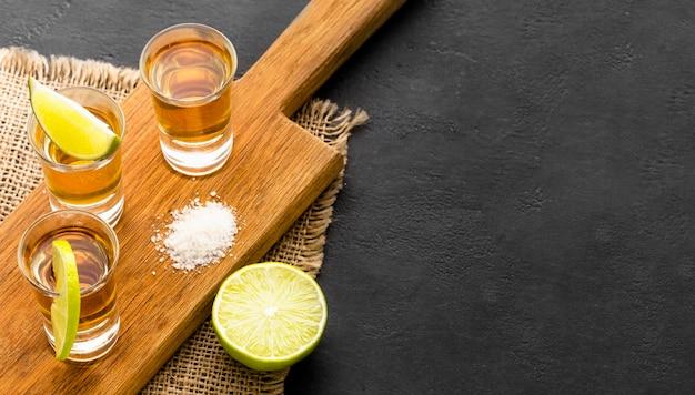 High angle tequila shots und limettenscheiben auf schneidebrett mit kopierraum