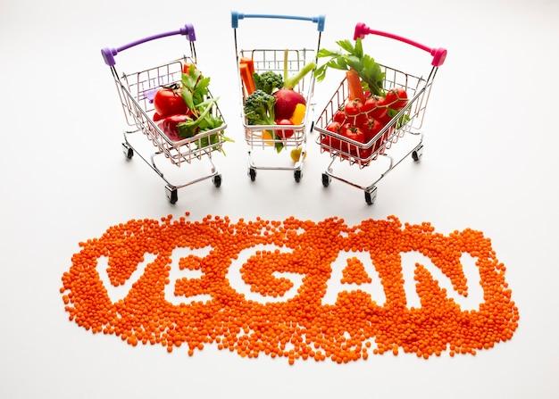 High angle vegan schriftzug mit leckerem gemüse in kleinen einkaufswagen