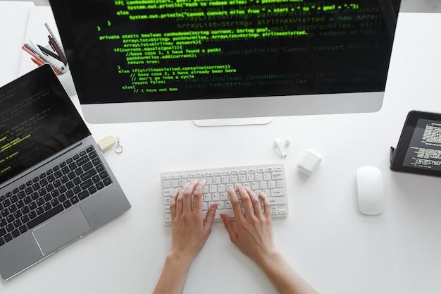 High angle view des entwicklers, der auf der computertastatur tippt und das neue system auf dem computer am tisch installiert