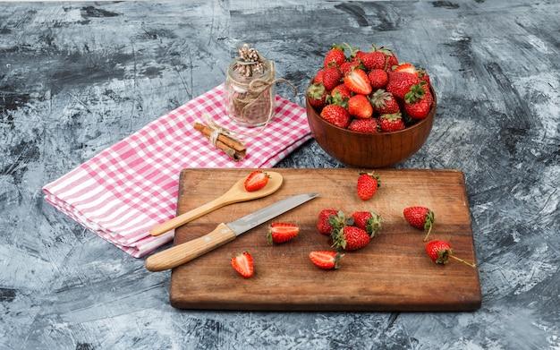 High angle view ein glas und zimt auf rotem gingham tischdecke mit küchenutensilien und eine schüssel erdbeeren auf dunkelblauer marmoroberfläche. horizontal