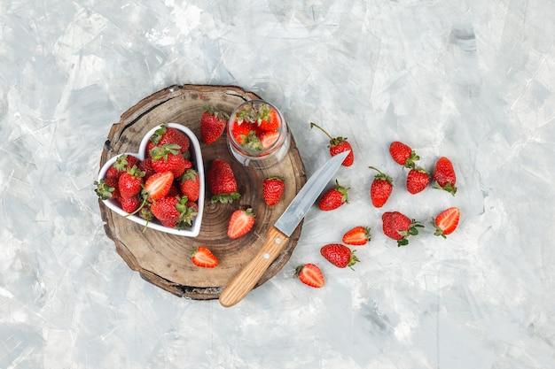 High angle view eine schüssel erdbeeren auf rundem korb tischset auf dunkelblauer marmoroberfläche. horizontal
