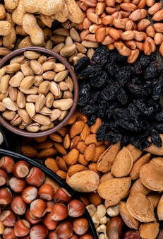 High angle view verschiedene nüsse und getrocknete früchte in verschiedenen schalen mit pekannuss, pistazien, mandel, erdnuss, cashew, pinienkernen. vertikale