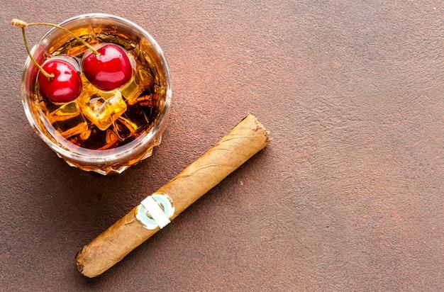 High angle whisky auf den felsen mit kirschen und zigarre mit kopierraum