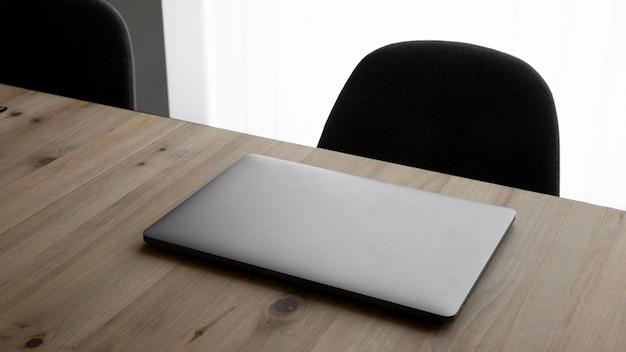 High angle workplace mit laptop und stühlen